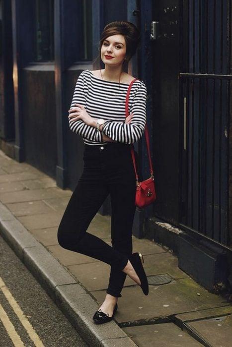 Chica modelando un conjunto de pantalón negro con blusa de rayas horizontales