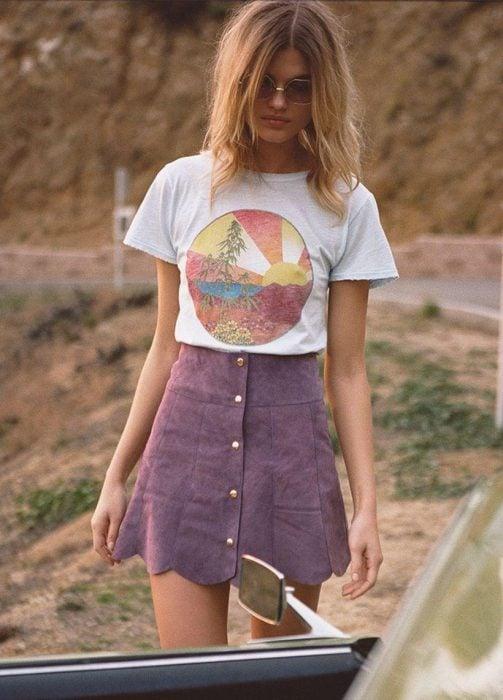 Chica en sesión fotográfica modelando una camiseta con estampado y una falda en forma de A color rosa