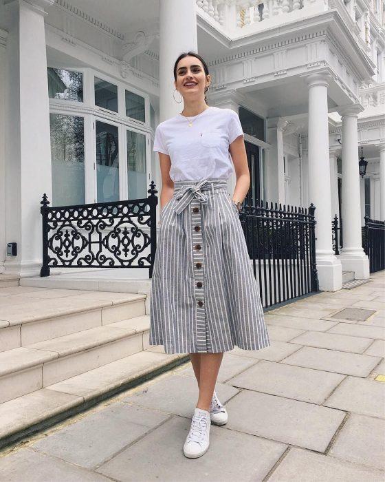 Chica modelando una falda con volumen, una camiseta blanca y tenis blancos