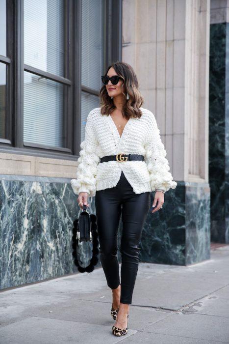 Chica caminando por la calle con saco blanco y cinturón negro, leggin negro, bolsa grande negra y lentes oscuros