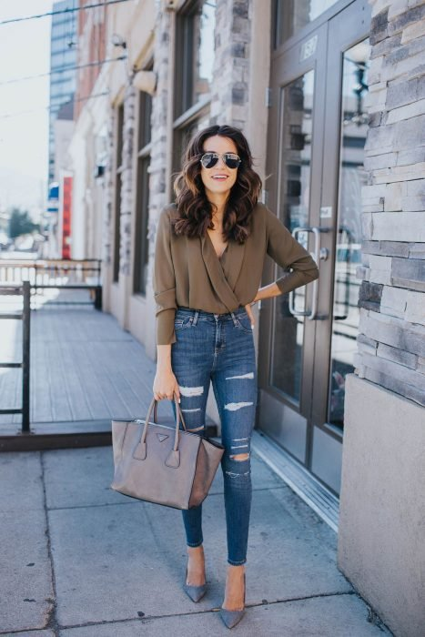 Chica con jeans de mezclilla, blusa color verde militar fajada, bolsa color gris y lentes negros