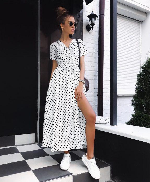 Chica modelando un wrap dress con tenis blanco y gafas oscuras