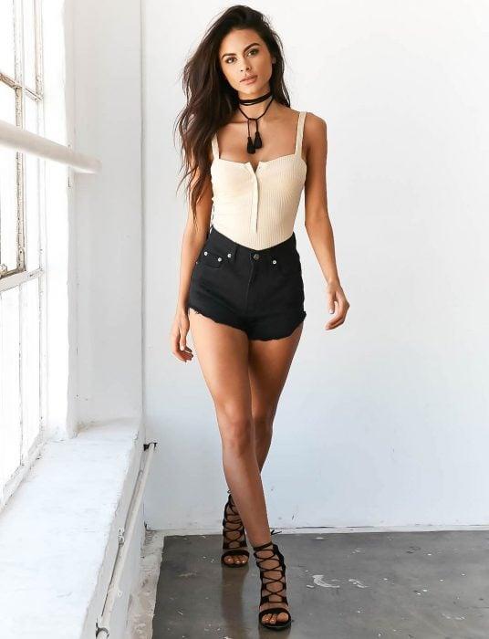 Chica modelando un short negro con un bodie de color piel de tirantes