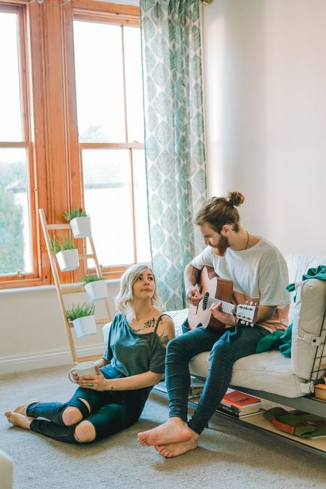 Pareja de novios sentados dentro de una habitación tocando la guitarra y bebiendo café