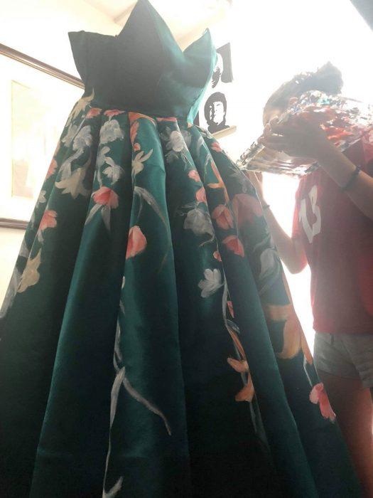Estidiante filipina Ciara Gan confeccionó su propio vestido de graduación ampón largo, color verde esmeralda con flores tigre anaranjadas y amarillas, chica pintando a mano su vestido de fiesta