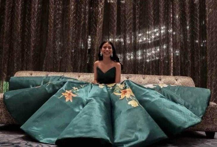 Estidiante filipina Ciara Gan confeccionó su propio vestido de graduación ampón largo, verde brócoli, con flores de tigre anaranjadas, chica sentada en el suelo con su gran vestido de princesa