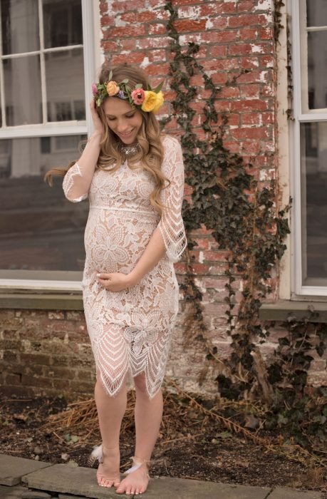 Vestido para baby shower, mujer embarazada con vestido corto de encaje color beige, descalza y con corona de flores en el cabello rubio