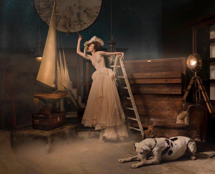 Vestidos de novia vintage confeccionados por la diseñadora Joanne Fleming, sesión de fotos anitguas, mujer parada en escaleras, con vestido al lado de un perro gran danés blanco con manchas negras y un barco de madera a escala