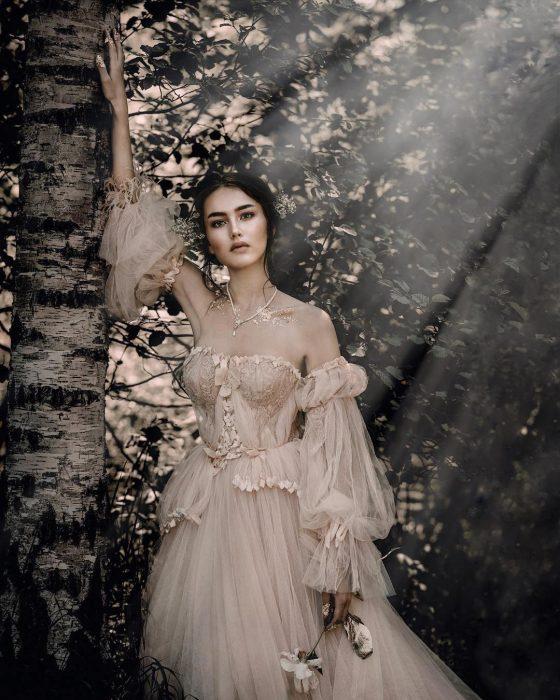 Vestidos de novia vintage confeccionados por la diseñadora Joanne Fleming, retrato de mujer al lado de un árbol con la luz del atardecer, usando vestido de tul vaporoso de color rosa pálido, sosteniendo una flor en la mano