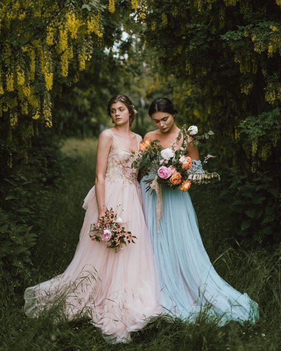 Vestidos de novia vintage confeccionados por la diseñadora Joanne Fleming, dos mujeres en medio del campo con vestidos elegantes vintage color rosa y azul de tela tul, sosteniendo un ramo de rosas en las manos