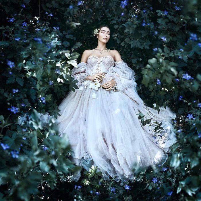 Vestidos de novia vintage confeccionados por la diseñadora Joanne Fleming, mujer entre plantas y flores, con los ojos cerrados y un vestido vaporoso de tela tul color gris