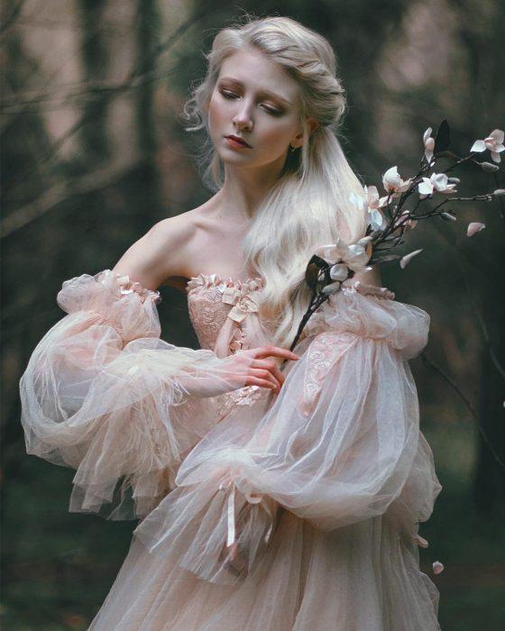 Vestidos de novia vintage confeccionados por la diseñadora Joanne Fleming, mujer rubia con vestido sin hombros, con mangas anchas sosteniendo una rama con flores