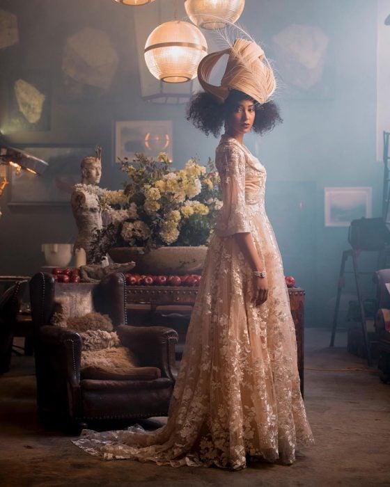 Vestidos de novia vintage confeccionados por la diseñadora Joanne Fleming, sesión de fotos antiguas con mujer morena con vestido rosa pálido largo, con mangas y encaje de flores, con un tocado de cabello con plumas, frente a un sillón de cuero café y un florero con claveles