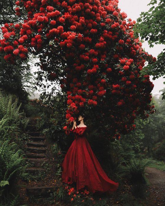 Vestidos de novia vintage confeccionados por la diseñadora Joanne Fleming, mujer bajo un gran árbol de bugambilias rojas, con vestido frondoso color rojo sin hombros