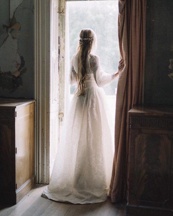 Vestidos de novia vintage confeccionados por la diseñadora Joanne Fleming, mujer de espaldas frente a una ventana, con vestido blanco largo de encaje