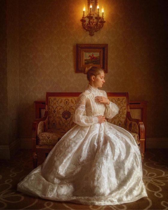 Vestidos de novia vintage confeccionados por la diseñadora Joanne Fleming, mujer con peinado chongo sentada en un sillón antiguo, usando vestido frondoso blanco de encaje, con mangas y cuello con botones