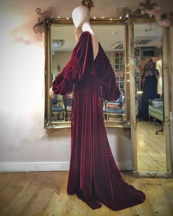 Vestidos de novia vintage confeccionados por la diseñadora Joanne Fleming, vestido largo de terciopelo rojo vino, con mangas anchas y sin espalda sobre un maniquí frente a un espejo