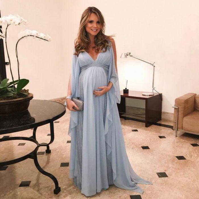 Vestidos para baby shower, mujer rubia embarazada con vestido azul estilo princesa con tul y bolsa de mano