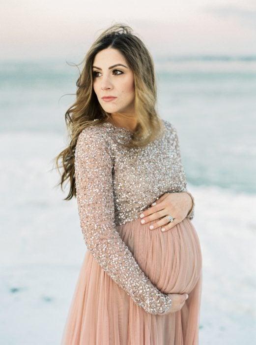 Vestidos para baby shower, sesión fotográfica de embarazo en la playa, mujer rubia de cabello largo con vestido rosa salmón y top de lentejuelas de manga larga