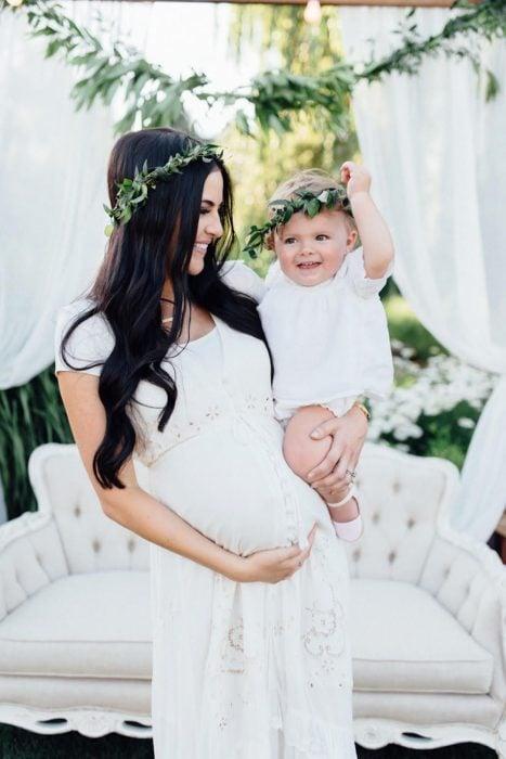 Vestidos para baby shower, mujer embarazada cargando a su bebé con ropa que combina, mamá con vestido blanco y corona de flores y bebé con ropón blanco