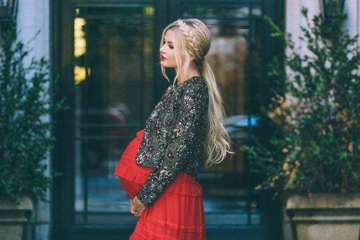 Vestidos para baby shower, mujer con vestido rojo y saco de pedrería en sesión de fotos de maternidad, peinado para cabello largo con corona de trenza y una coleta