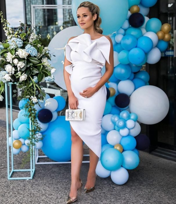 Vestidos para baby shower, mujer rubia con coleta, embarazada con vestido blanco, ceñido al cuerpo y con holanes en el pecho, tacones dorados y bolsa pequeña de mano, parada frente a globos azules