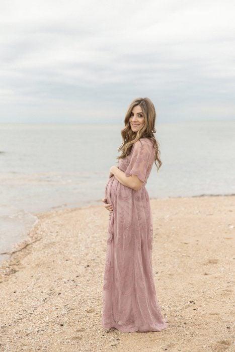 Vestidos para baby shower, mujer embarazada en sesión fotográfica de maternidad en la playa al aire libre, con vestido rosa pálido con encaje y tela de tul