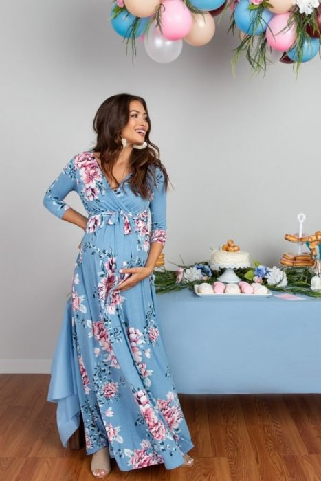 Mujer de cabello castaño embarazada, usando vestido azul, largo y holgado de flores rosas, festejando baby shower de niño