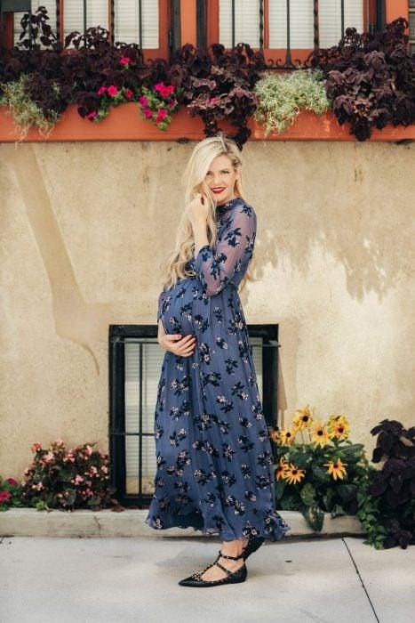 Vestidos para baby shower, mujer de cabello rubio, largo hasta la cintura, embarazada usando vestido azul grisáceo con pequeñas flores, sandalias negras de piso con estoperoles