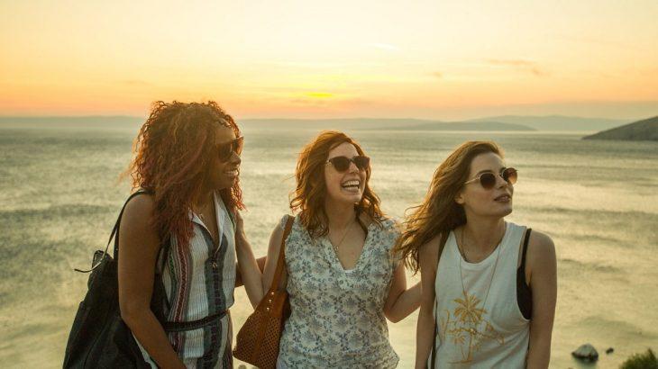 Tres chicas disfrutando de la conversación en la playa