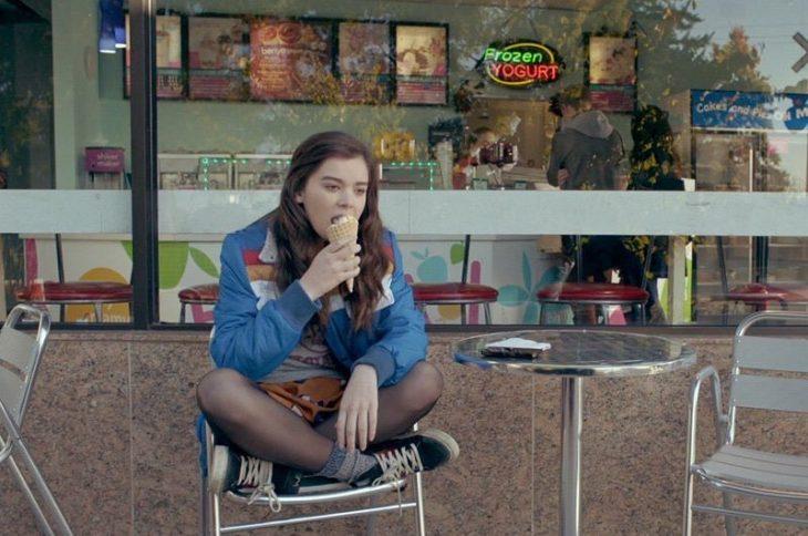 Chica sentada sola afuera de una tienda mientras come un helado