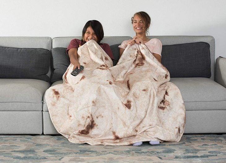 Dos chicas sentadas en un sillón con una cobija impresa de tortilla de harina mientras ven televisión