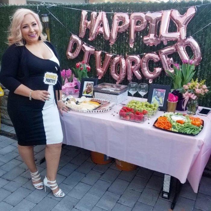 Mujer parada junto a una mesa de postres mientras festeja su feliz fiesta de divorcio