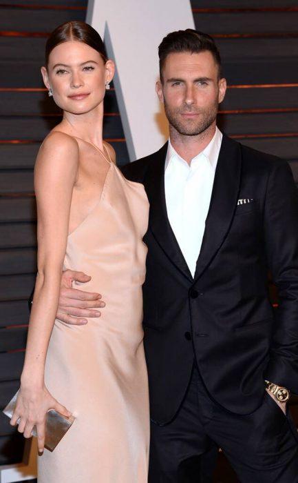 Adam Levine y Behati Prinsloo abrazados durante la alfombra roja de los premios Óscar