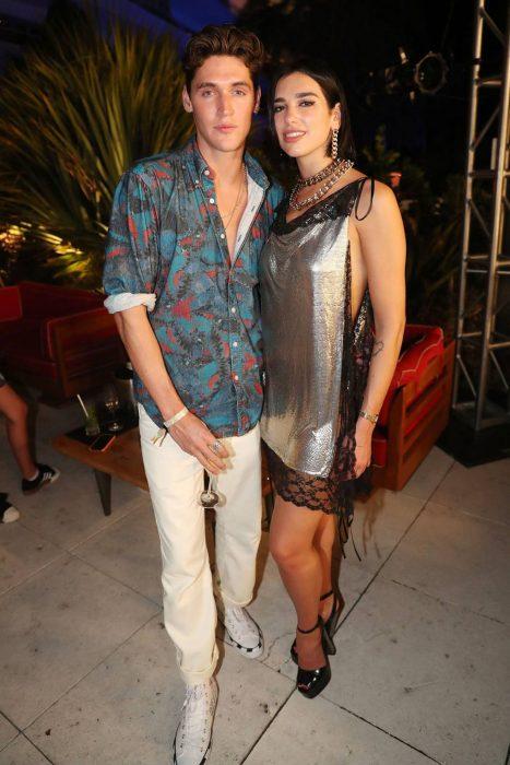 Dua Lipa e Isaac Carew abrazados posando para una foto durante una fiesta