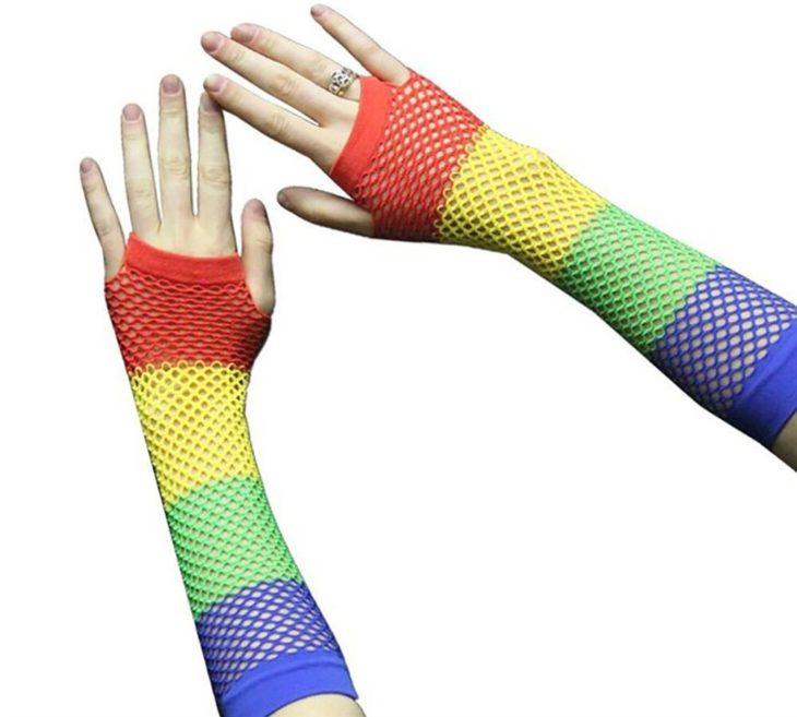 Chica usando guantes de maya de colores azul, amarillo, verde y rojo