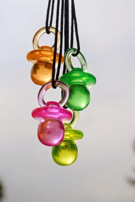 collares con figuras de chupones plásticos de colores verde, naranja y rosa