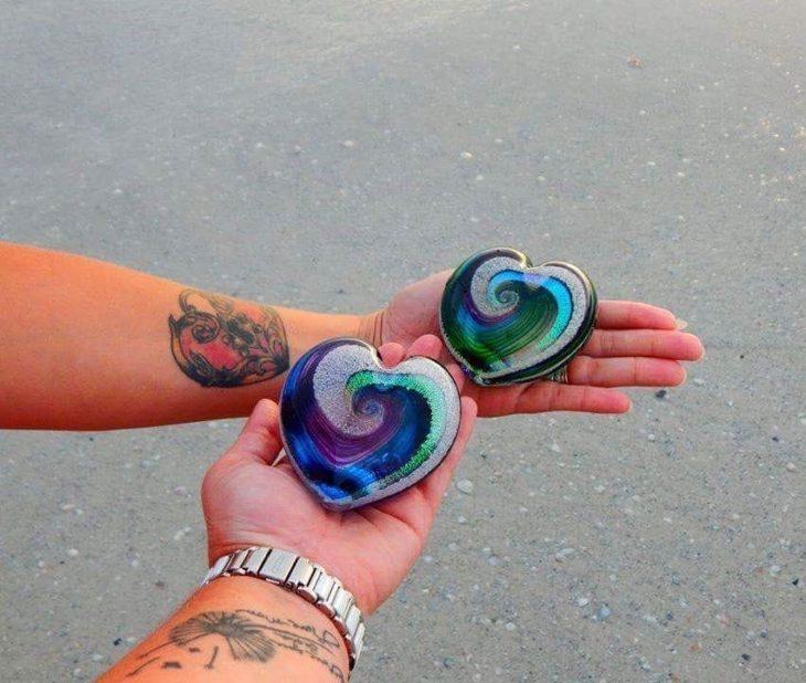 Artful ashes crea figuras de vidrio soplado con cenizas de seres queridos; mujer y hombre con tatuajes sosteneiendoadorno de cristal en forma de corazón color verde, azul y morado