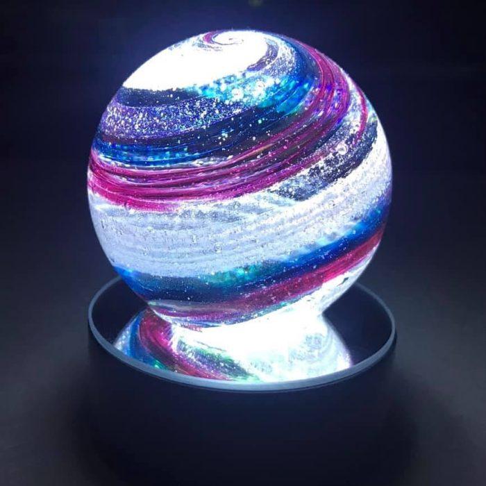 Artful ashes crea figuras de vidrio soplado con cenizas de seres queridos; adorno de cristal en forma de esfera color morado y azul