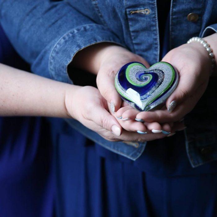 Artful ashes crea figuras de vidrio soplado con cenizas de seres queridos; adorno de cristal en forma de corazón color azul, verde y blanco entre manos