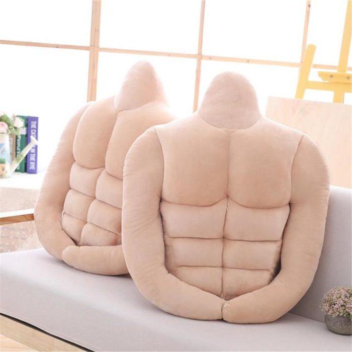 Par de almohadas colocadas en un sofá. Tienen forma de hombre con sixpack y brazos