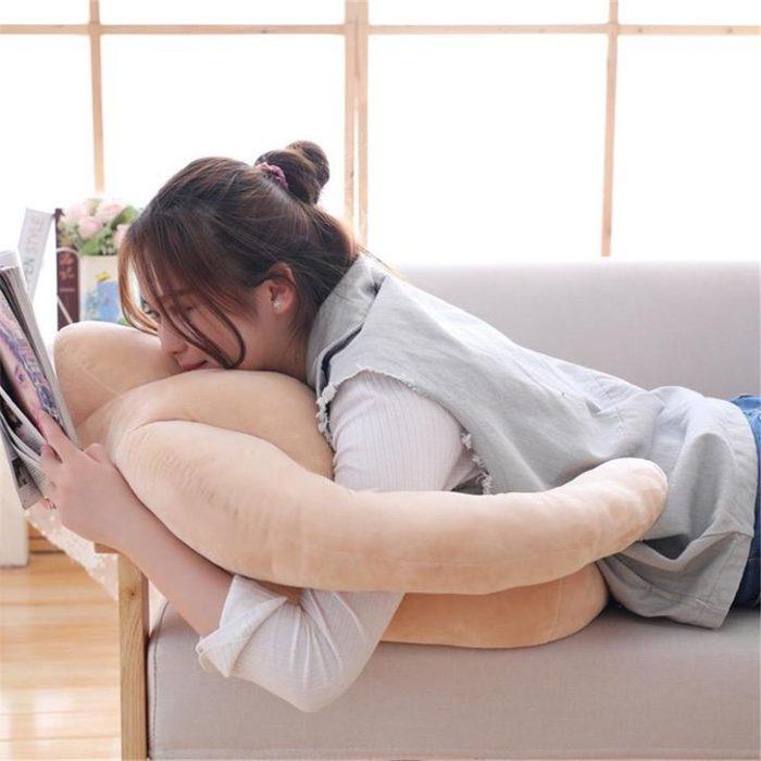 Chica durmiendo sobre una almohada en forma de hombre mientras está leyendo una revista