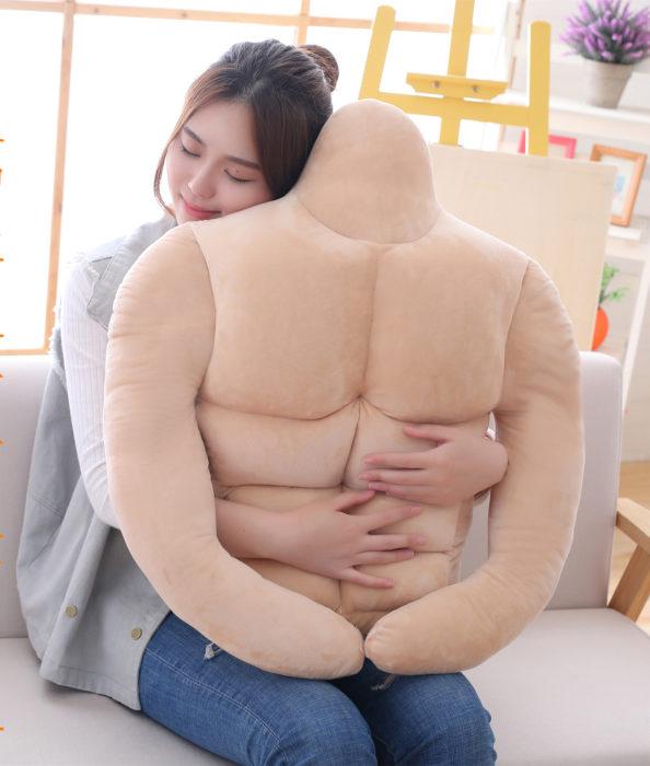Chica abrazando una almohada en forma de hombre musculoso