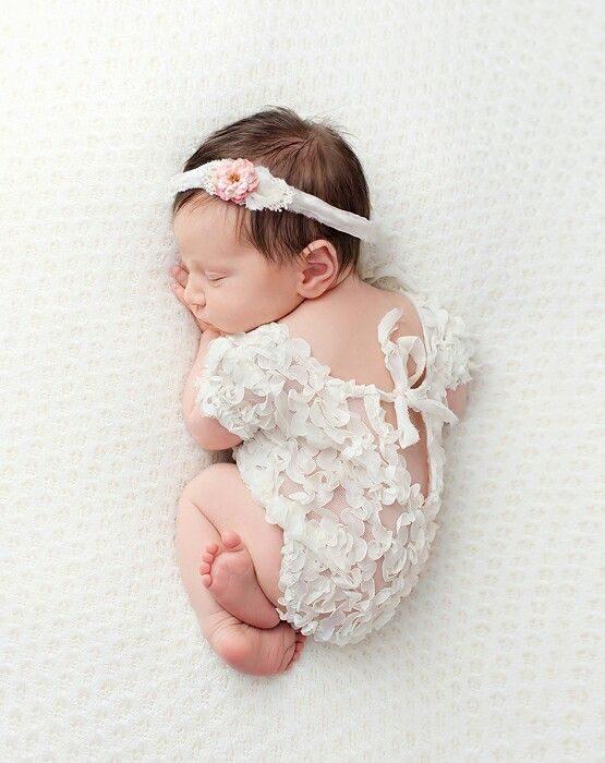 New born con temática de encaje bebé niña acotada de lado sobre una sabana blanca