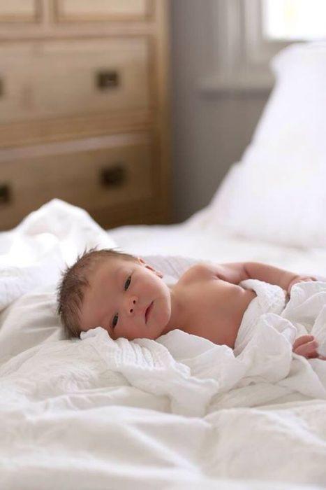 Bebé envuelto en sabanas blancas acostado en la cama