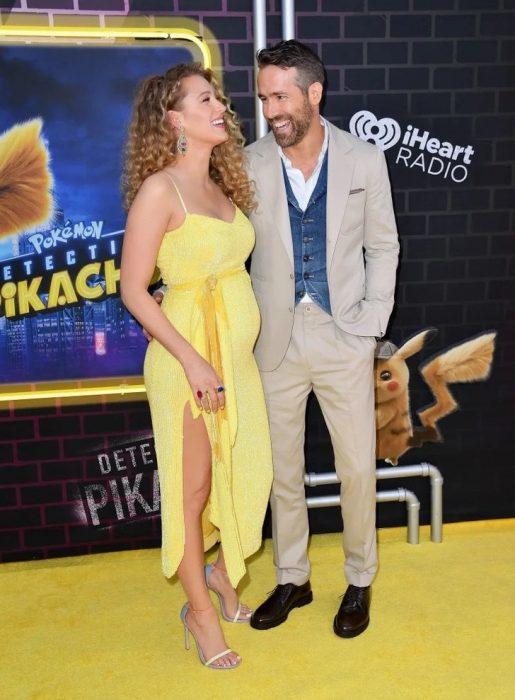 Blake Lively y Ryan Reynolds abrazados, posando para una foto durante la alfombra amarilla del estreno de Detective Pikachu