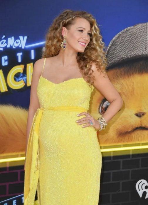 Blake Lively modelando un vestido amarillo y mostrando su pancita de embarazada durante la alfombra amarilla del estreno de Detective Pikachu