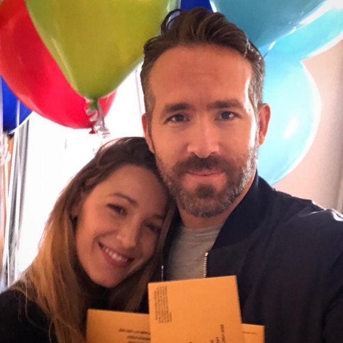 Blake Lively y Ryan Reynolds abrazados mostrando sus globos y tarjetas de feliz cumpleaños