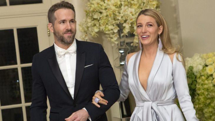 Blake Lively y Ryan Reynolds tomados de la mano, llevando ropa elegante mientras caminan por una alfombra roja