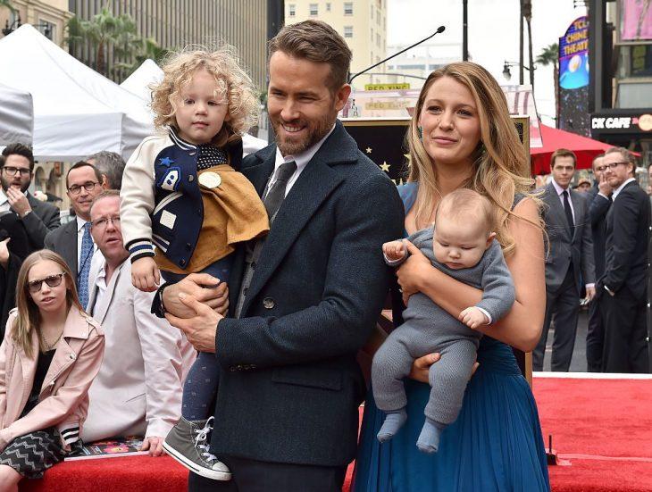 Blake Lively y Ryan Reynolds cargando a sus hijas Inez y James durante una alfombra roja